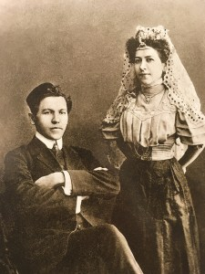 A man in suit and high collar sits, whil a woman in a dark skirt, light blouse with puffed sleeves, and a lace headdress and silver jewelry/tiara stands next to him.
