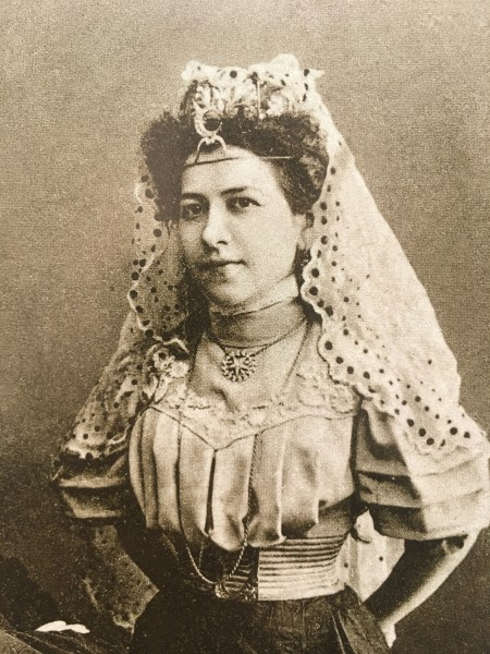A handsome woman in a dark skirt, light blouse with puffed sleeves, and a lace veil held by an elaborate silver headdress/tiara with a moon and stars on her forehead, smiles placidly at the camera.