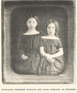 Two young girls in dark, boatneck dresses sit facing the camera
