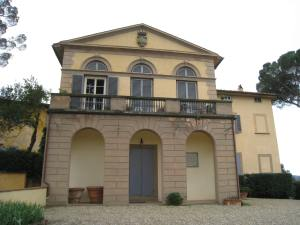 A two-story home with balcony and newer-looking ground floor archways in Florence