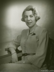 Marjorie Hillis, a white woman with short blonde hair and wearing a beige suit-dress, sits in a chair and smiles at the camera. Author of Live Alone and Like It