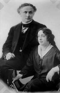 A man and woman sit beside one another. The man has light eyes and a striking expression, staring directly at the viewer. He wears a formal suit and waistcoat, pocket watch and bow tie. The woman wears a loose suitdress with white collar and brooch, pearl necklace and fashionable, early 20th century short haircut.