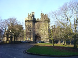 """A tall, imposing stone castle with two turrets, a large """"drawbridge"""" style gate adn surrounded by green parkland and trees."""