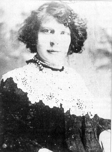 A young woman in a black dress with wide lace collar and trim smiles confidently at the camera. Her hair is up and her eyes are bright, staring straight at the onlooker.