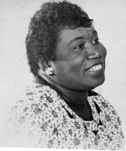 An African-American woman smiles at something to the right of the camera. She is wearing a white patterned blouse and earrings, and her hair is short-cropped