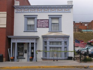 """A striking white brick two story building with grey and pink trim on porch, bow window, and upper story deocrations. A sign on the front of the building reads """"The Old Homestead House Museum"""""""