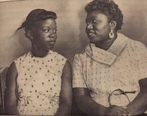 An African American woman and girl look at one another while seated next to one another. Mae Mallory is wearing a fashionable patterned white dress and holding a handbag, Patricia is wearing a white patterend sleeveless dress and pigtail braids.