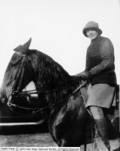 A young woman wearing dark jacket, light-colored skirt, riding boots and a cloche-style hat smiles at the viewer from astride a large black horse, reigns in hand.