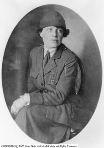 A white woman in a military-style coat, skirt and hat stares to the right of the viewer with a pleasant, confident expression. She wears a Croix de Guerre medal on her jacket,a French military honor. She has short dark hair and light eyes.