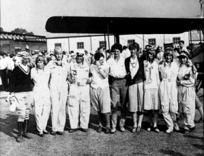 A large group of female pilots stands on an airfield