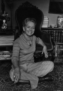 A middle-aged woman in light-colored trousers and a striped sweater sits on the floor in front of a formal armchair.