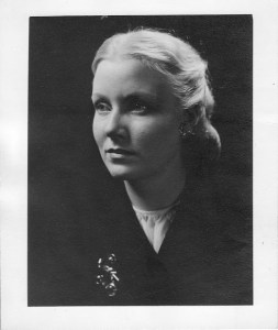 A formal black and white portait of a beautiful woman wearing a black suit jacket and silver brooch.