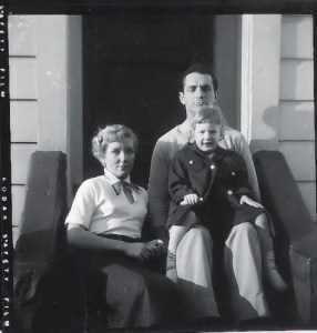 A woman wearing a white blouse and black skirt sits on a front step next to a man in light colored shirt and khaki trousers. A toddler girl in a black peacoat sits on the man's lap, smiling happily.