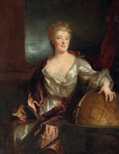 A woman in 18th century dress with light red hair and a white dress and red-brown velvet drape