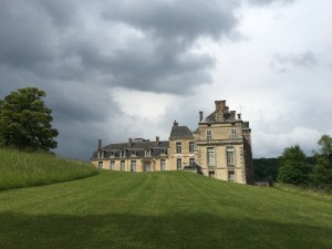 A castle-chateau stands on a green hill