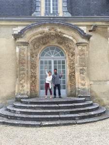 Two people stand in front of a formal double door surrounded with carved stone archways and floral motifs