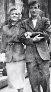 A young couple stand arm in arm, smiling happily. She wears a fashionable wool jacket and skirt, he wears a slightly rumpled-looking brown suit.