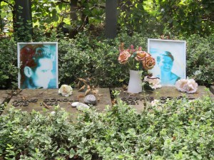Two stone markers flat on the ground bear the names of Sophie and Hans Scholl. Photos of each are standing on the stone, and they are surrounded by greenery and flowers from visitors.