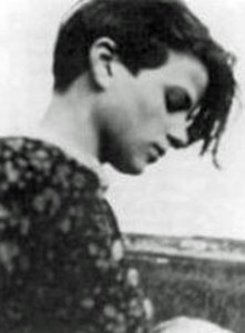 A young woman with a short, asymetrical haircut and a floral shirt stares pensively down in profile