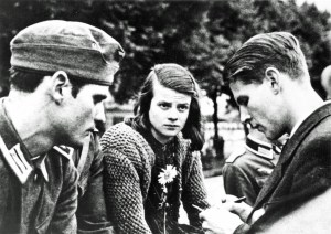 Three young people in 1940s dress sit facing one another oudoors, engaged in conversation.