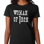 """A black t-shirt with the words """"woman of iron"""" in white lettering. The """"I"""" in iron is a railroad spike. for for Ogden Audio History Tours"""