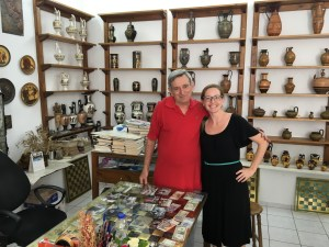 A man and woman stand in front of shelves of replica Greek vases and statuary