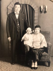A Chinese American woman holds a baby seated next to a man standing to their right