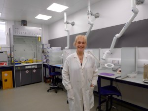 Dr Montgomery in a scientific lab. She wears a white lab coat and is smiling at the camera.