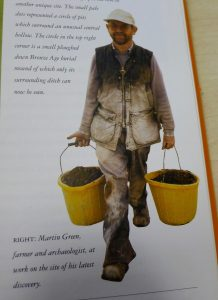 A man in brown clothing, covered in white chalk, walks carrying two large yellow buckets full of earth. He is smiling.