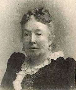 Portrait of Mary Donelson Wilcox: A middle-aged woman wearing black dress, white ruffled collar, large pearl drop earrings and with graying hair styled up and off the neck and face smiles pensively past the camera.