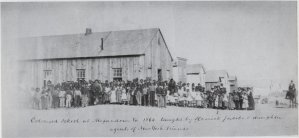 A large group of black and mixed-race students stand in front of a large wooden building, looking toward the camera