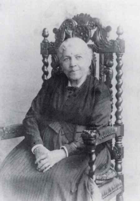 An elderly woman wearing a black gown in 19th century style sits in an ornately carved armchair, smiling at the camer. Her hands are clasped in her lap.
