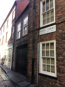 A sign on a brick building reads King's Court.