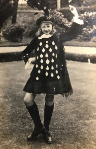A girl in a black dress covered in silver medals strikes a highland dancing pose