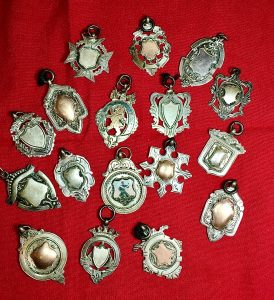 A group of ornate silver medals on a red velvet background