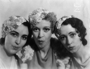 """Three white women in 30s-style floral """"fascinator"""" hats lean in to the center, their lips pursed as if singing."""