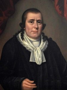 Oil portrait of Publick Universal Friend. Friend wears a black robe, white scarf, and has long ringlets around the ears and cut short on top.