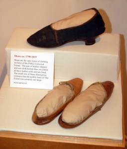 Two brown leather slippers and a black cloth heeled shoe sit on a display case. A card points out their very small size.