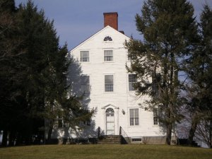 A three-story white home in colonial style stands surrounded by trees.