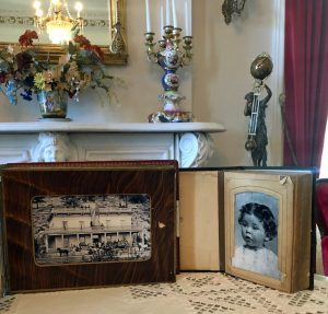 An antique photo album open to a photo of a young toddler sits on a table next to a photo of the Bowers Mansion. She has light skin and dark curly hair.