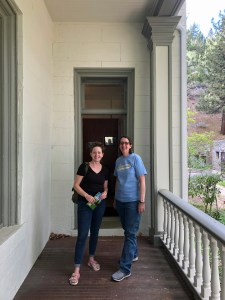 Two women stand on a front porch of a white brick house.
