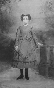 A sepia photo of an approximately ten year old girl with dark hair standing in front of a victorian photo backdrop. She is wearing a calf-length dress wtih long sleeves and an intricately pieced wool skirt.