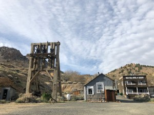 A small frame building sits in the desert next to an antique wooden mining frame (for hauling people and ore up out of the shaft) and a few other old wooden frame buildings in the background.