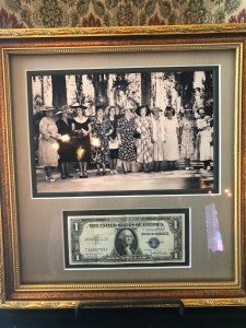 A photo of a group of women in mid-20th century dress, framed above a one-dollar bill.