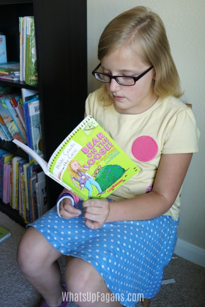 Picture of a young girl reading a book at home - great way of encouraging your child to read