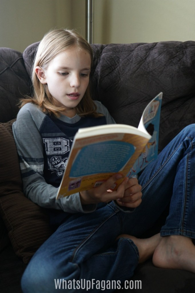 picture of young girl reading a book at home for post about ideas to encourage reading