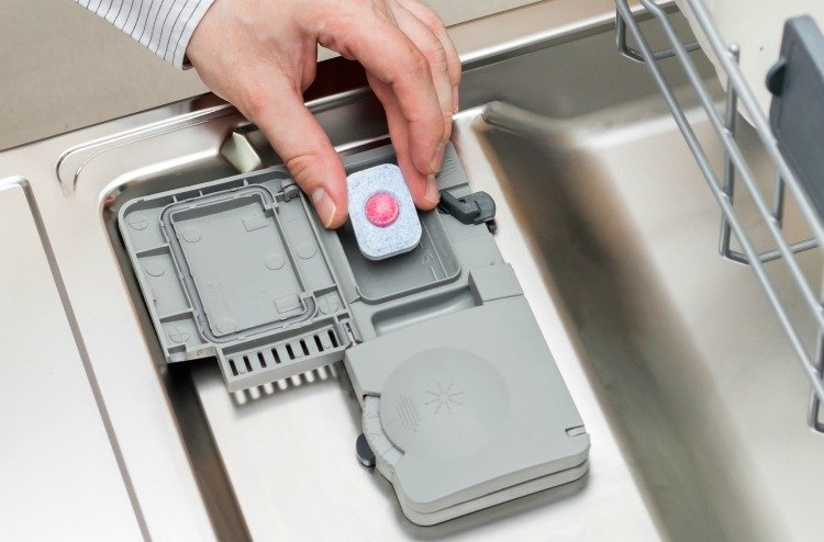 Man hand putting tablet in dishwasher detergent box
