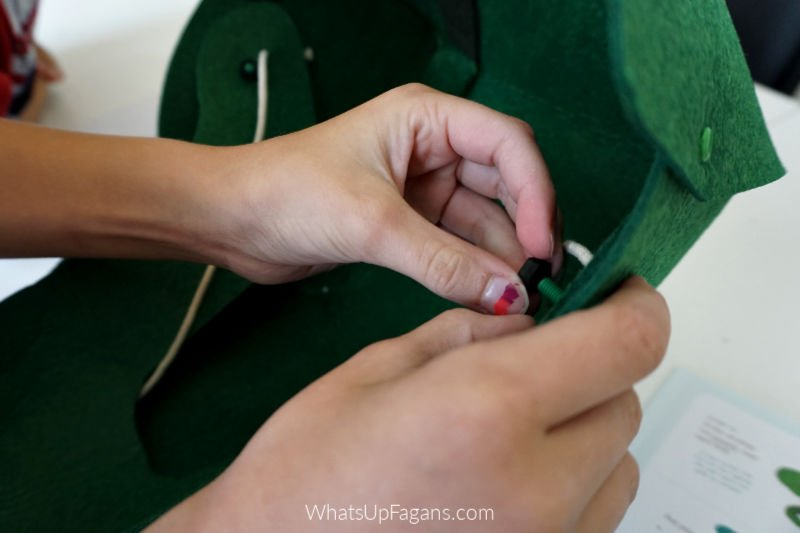 little girl hands assembling Kiwi Crate T rex costume DIY