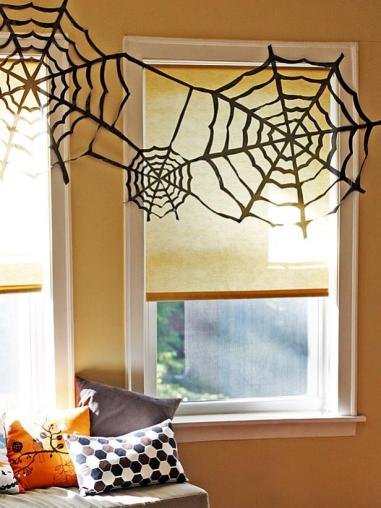 easy spooky Halloween decorations using black garbage bags to create spider webs