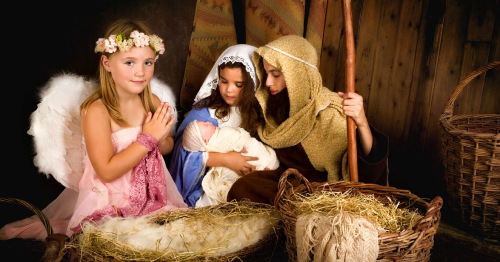 cute little girls acting out nativity scene wearing angel nativity costume, mary nativity costume, and joseph nativity costume
